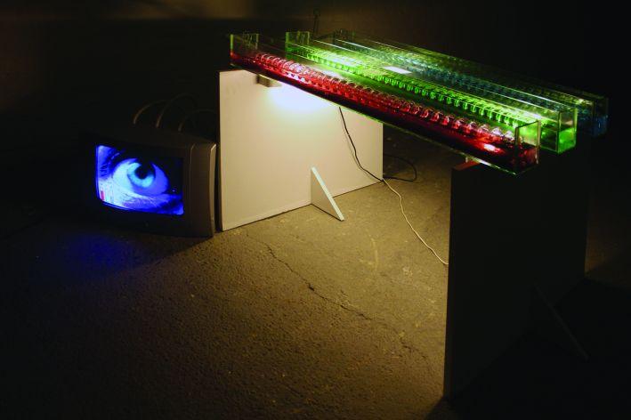 II. számú fölösleges kísérlet – RGB (2006, három üvegedény, üvegspirál, bútorlap, neon, tévé, DVD loop, gégecső, színes folyadékok, vezetékek, 120×100×75 cm)