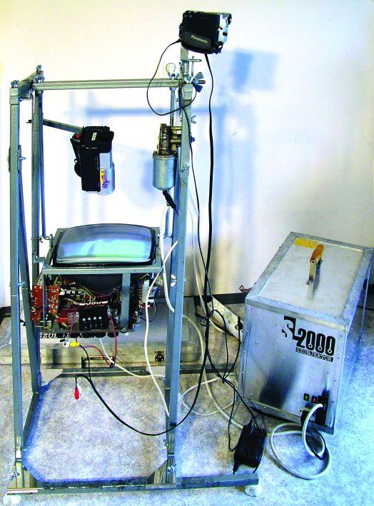 SL-2000 szubjektor (2004, acélszerkezet, alumínium dobozok, tévé, kamerák, projektor, villanymotor, elektromos alkatrészek, vezetékek, 124×45×52 cm)